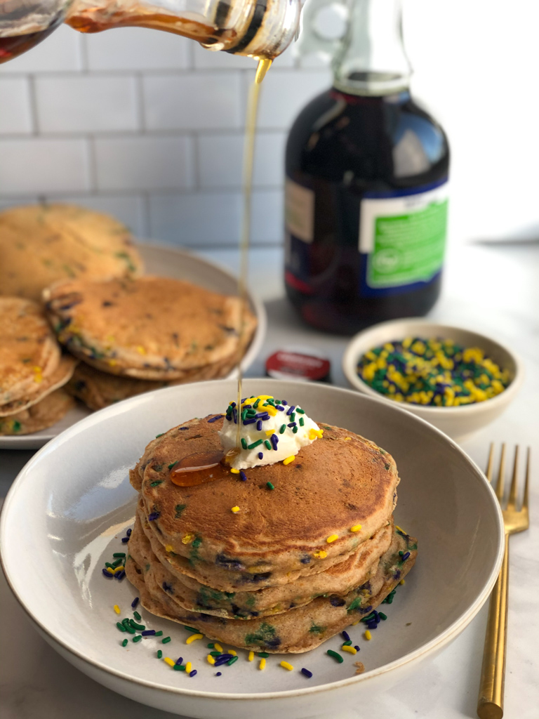 Pouring maple syrup over Stack of healthy greek yogurt spelt pancakes with mardi gras sprinkles